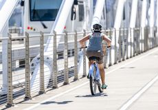 Woman rides a bicycle with a basket on Tilikum Crossing Bridge preferring a healthy lifestyle
