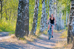 A woman rides a bicycle on a footpath in a city pa Royalty Free Stock Photo