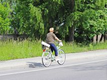 A woman rides a bicycle on the side of the highway against a background of green trees on a sunny, clear day. Alternative Masow ty. Pe of daily transport. A stock photography