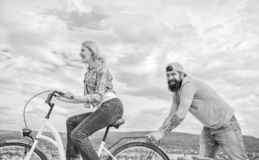 Woman rides bicycle sky background. Push and promoting. Impulse to move. Man pushes girl ride bike. Support helps. Believe in yourself. Feel impulse to start stock image