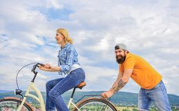 Woman rides bicycle sky background. Push and promoting. Impulse to move. Man pushes girl ride bike. Support helps. Believe in yourself. Feel impulse to start stock photo