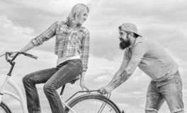 Woman rides bicycle sky background. Service and assistance. Man helps keep balance ride bike. Girl cycling while man. Woman rides bicycle sky background. Service stock photo