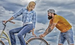 Woman rides bicycle sky background. Service and assistance. Man helps keep balance ride bike. Girl cycling while man. Woman rides bicycle sky background. Service royalty free stock photography