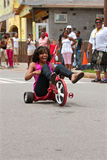Woman Rides Big Wheel Tricycle Down Atlanta Street. Atlanta, GA, USA - August 3, 2013: An unidentified young woman rides downhill on a Big Wheel at the Cool Dads royalty free stock photo