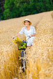 Woman rides cycle with apples and flowers in rye field Stock Photo