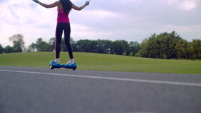 Woman rides gyroscooter on park road. Girl using self balancing gyro scooter stock footage