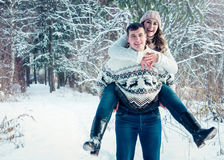 Woman rides on her boyfriend`s back. In winter forest Royalty Free Stock Photos