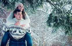 Woman rides on her boyfriend`s back. In winter forest Royalty Free Stock Images