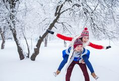 Woman rides on her boyfriend`s back. In winter forest Royalty Free Stock Image
