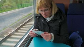 A woman rides the high-speed train sitting at the window and checks the tickets. stock footage