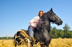 Woman rides pretty black horse in field Royalty Free Stock Images