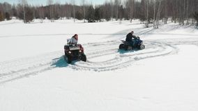 A woman rides a quad around a man on a snow-covered field. A woman rides a quad around a man on a snow-covered field - On the forest stock footage