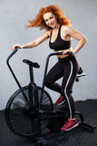 Woman riding the air bike. Young athletic woman riding the air bike at the gym Royalty Free Stock Image
