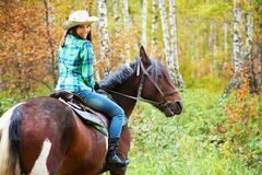 Woman riding. Attractive smiling woman in a hat riding a horse Royalty Free Stock Images