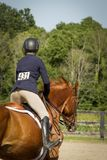 Woman riding away on chestnut gelding. In a horse show arena Stock Image