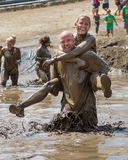 Woman riding on the back of a man at the Dirty Dash Stock Photo