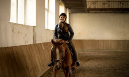 Woman riding beautiful brown horse at indoor manege Stock Photos