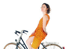 Woman riding bicycle. Young woman riding bicycle in orange summer dress royalty free stock photos