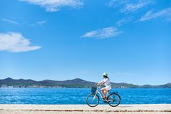 Woman riding a bicycle along stony sidewalk on blue sparkling sea water. Girl cyclist in white summer closing and hat riding a bicycle along stony sidewalk on royalty free stock photography