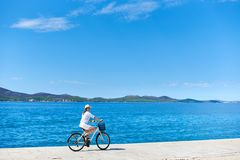 Woman riding a bicycle along stony sidewalk on blue sparkling sea water. Happy woman in white summer closing and hat riding a bicycle along stony sidewalk on royalty free stock photography