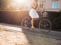 Woman riding bicycle along the street. Cropped shot of woman riding bicycle along the street. Female cycling on road with sun flare royalty free stock photo