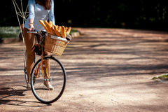 Woman riding the bicycle with the basket full of baguettes on th Stock Image