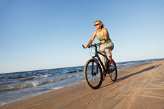 Woman riding bicycle in beach Stock Photos