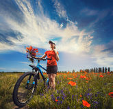 Woman riding a bicycle on a blooming poppy meadow Stock Photos