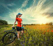 Woman riding a bicycle on a blooming poppy meadow Royalty Free Stock Photography