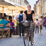 Woman riding bicycle in city center. Royalty Free Stock Photography