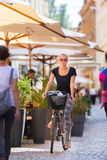 Woman riding bicycle in city center. Stock Photos