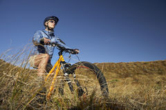 Woman Riding Bicycle In Field Stock Image