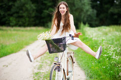 Woman riding bicycle with her legs in the air Royalty Free Stock Images