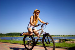 Woman riding bicycle with her legs in the air stock photography