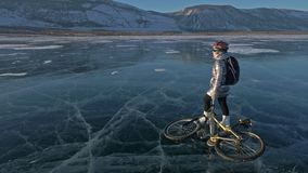 Woman is riding bicycle on the ice. The girl is dressed in a silvery down jacket, backpack and helmet. The cyclist rides. Woman is riding bicycle on the ice. The stock footage