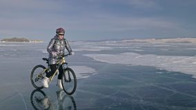 Woman is riding bicycle on the ice. The girl is dressed in a silvery down jacket, cycling backpack and helmet. Ice of. The frozen Lake Baikal. The tires on the stock footage