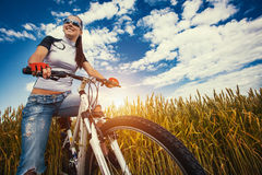 Woman is riding bicycle outside in the field Royalty Free Stock Images