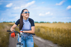Woman is riding bicycle outside in the field. Happy Young Woman riding bicycle outside. Healthy Lifestyle Stock Photo