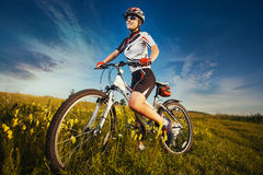 Woman is riding bicycle outside in the field Royalty Free Stock Photo