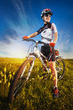 Woman is riding bicycle outside in the field Royalty Free Stock Photos