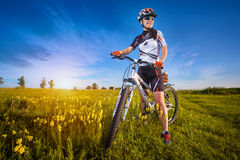 Woman is riding bicycle outside in the field Stock Photo