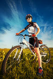 Woman is riding bicycle outside in the field Royalty Free Stock Image