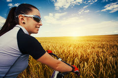 Woman is riding bicycle outside in the field Stock Photography