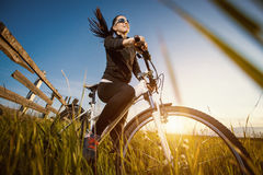 Woman is riding bicycle outside Stock Photos