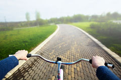 Woman riding a bicycle in park, handlebar view. Royalty Free Stock Photography