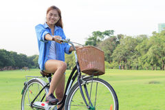 Woman riding bicycle in park, outdoor Stock Image