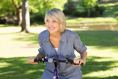Woman riding bicycle in parkland Royalty Free Stock Image