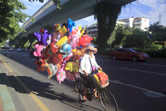 Woman riding a bicycle selling balloons Stock Photos