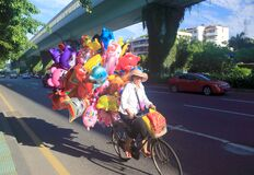 Woman riding a bicycle selling balloons, srgb image.