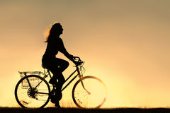 Woman Riding Bicycle Silhouette. A silhouette of a happy woman outside riding a vintage bicycle, isolated in front of a sunset in the sky.  Copyspace Stock Photo